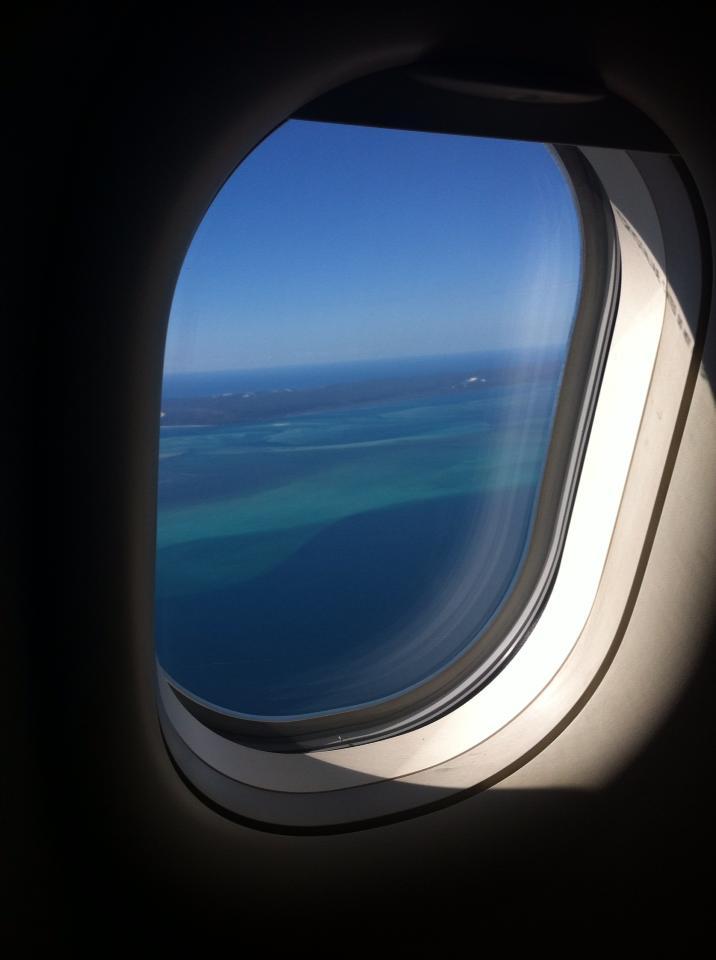 ragazza che guarda il mare dal finestrino in aereo