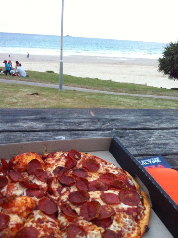 ragazza che mangia la pizza guardando il mare