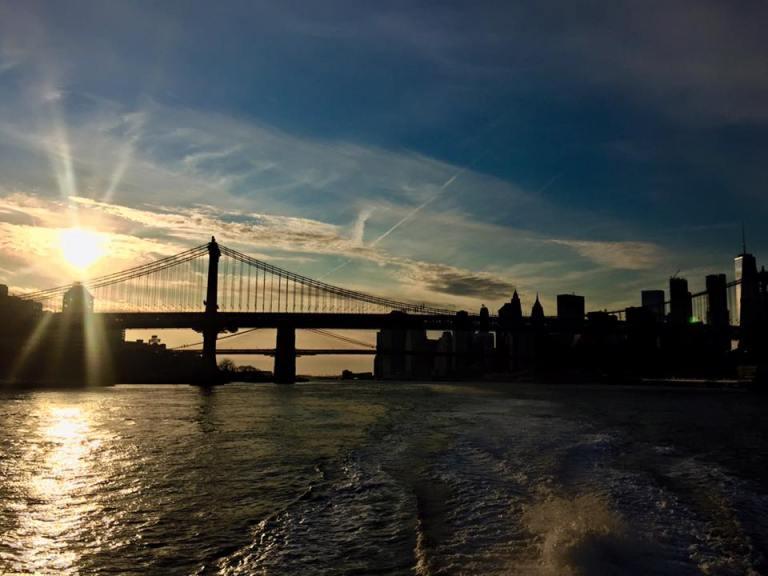 ragazza che guarda il tramonto su Manhattan Bridge dal traghetto