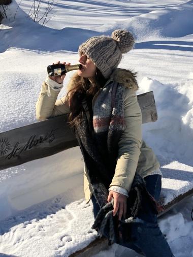 ragazza beve la birra su una panchina